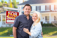 Happy Couple In Front of Sold Real Estate Sign and Beautiful House