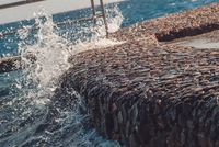 Giant Ocean waves hitting stone pier during storm. Vacation summer fresh picture