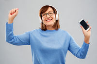 senior woman in headphones listening music on cell