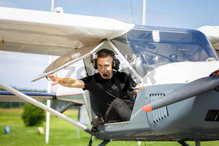 outdoor shot of young man in small plane cockpit