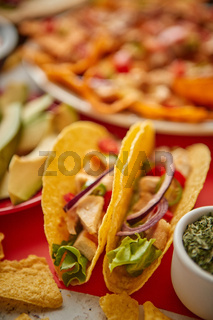 Close up on crispy tacos with various freshly made Mexican foods assortment