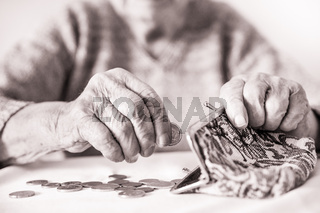 Detailed closeup photo of unrecognizable elderly womans hands counting remaining coins from pension in her wallet after paying bills.