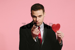 Handsome man in a black suit holding a red heart pointing at camera
