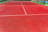 Background of a red cement tennis court in full sun in summer.
