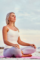 Attractive middle-aged woman do meditation on nature