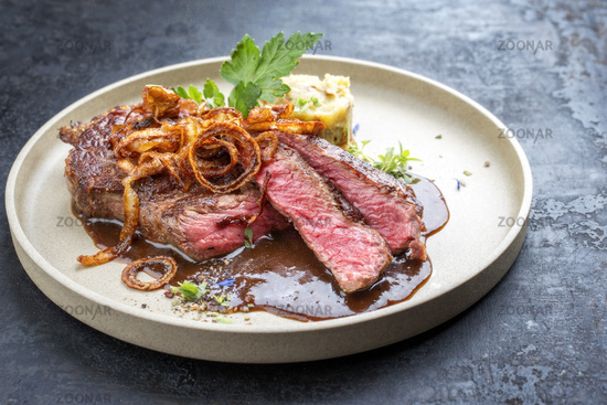 Modern design dry aged sliced roast beef with fried onion rings and mashed potatoes as closeup on a plate with brown sauce