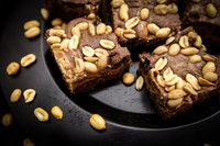 Homemade brownies with peanuts on a dark brown plade