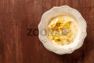 Italian tortellini in a cream sauce with Parmesan cheese, shot from the top on a dark rustic wooden background with a place for text