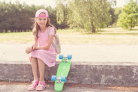 Happy girl child with skateboard