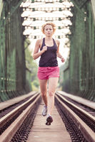 Active sporty woman running on railroad tracks.