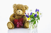 A teddy bear with a heart next to a vase of flowers. Spring is here.
