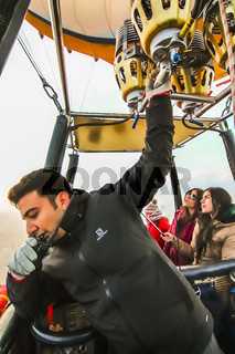 A hot air balloon pilot with one hand on walkie-talkie and the other on the burner