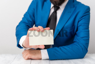Man holds empty paper with copy space in front of him. Business concept with man in a suite and a tie. White space for advertising message.