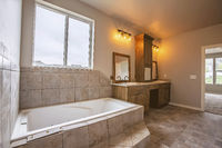 Built in bathtub in front the window of a bathroom with tiled floor and wall