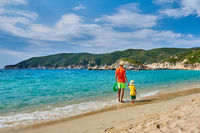 Toddler boy walking on beach with father