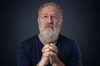Senior with beard praying