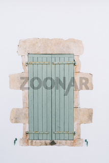 Old window with wooden light green painted shutters