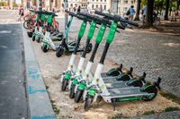 Row of parked electric E scooters , escooter or e-scooter of the  company LIME on sidewalk in Berlin