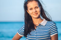 Beautiful and young girl in a striped blue dress stand against the backdrop of the blue sea and blurred beach coast line with palms. She smiles straight to the camera