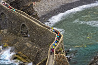 Visitors crossing the stone bridge to  the islet Gaztelugatxe near Bakio,Basque Country, Spain