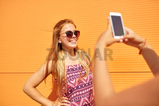 teenage girl photographing friend by smartphone