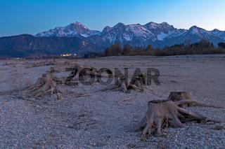 Baumstumpf im ausgetrockneten Forggensee nach Sonnenuntergang mit Blick nach Fuessen