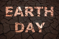 Earth Day text on dry cracked soil.