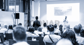 Businessman in audience standing and asking question to speeker at business conference.