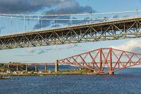 Older Forth Road bridge and the iconic Forth Rail Bridge in Edinburgh Scotland.