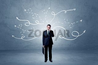 Businessman standing with winding arrows around
