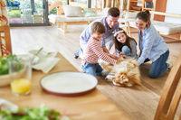 Familie und Kinder spielen mit dem Hund