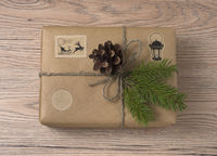 Christmas or New Year gift boxes wrapped in kraft paper with fir branch on wooden background.