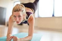 Junge Frau macht Gymnastik auf der Yoga Matte