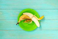 Peeled banana in a green plate