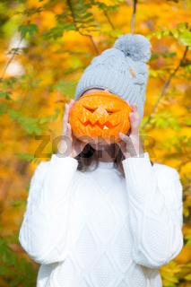 Teenage girl holding halloween pumpkin