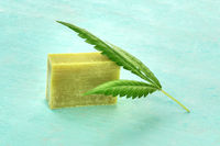 Homemade hemp soap bar with a cannabis leaf on a teal blue backgrround with copy space