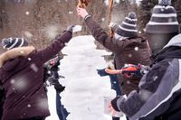 group of young people making a snowman