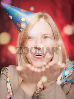 Attractive woman blowing confetti and celebrating