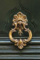 Detail of a bronze metal knocker on a wooden door of house