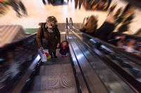young mother and her little daughter on escalator in shopping mall