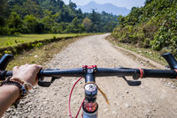 Riding a bicycle over dirt road, first person view