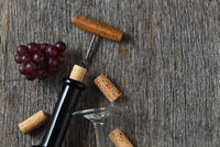 Wine still life with bottle corkscrew, grapes on a rustic wood table. Horizontal with copy space on