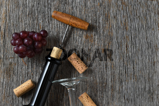 Wine still life with bottle corkscrew, grapes on a rustic wood table