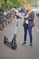 Young blond woman standing near electric kick scooter