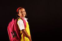 Little girl in school uniform and bag and tiffin posing in front of camera. Pune, Maharashtra