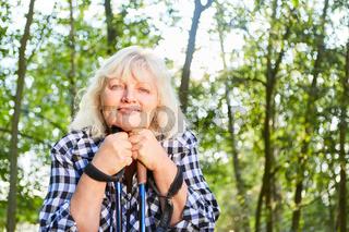 Glückliche Senior Frau beim Nordic Walking