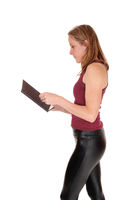 Woman standing in profile reading her book