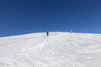 Skier downhill on snowy ski slope in sunny winter day