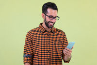 Happy young bearded Persian hipster man using phone