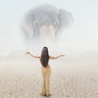 Fantasy fashion portrait of young woman posing in front of giant elephant